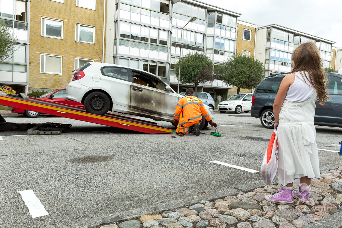 A burned out car being pulled away in Malmö